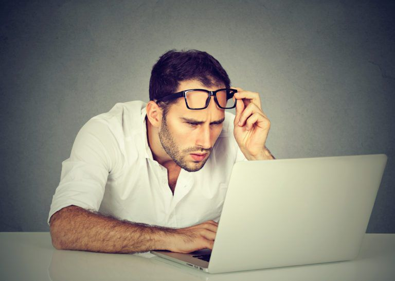 man having a hard time reading what is on his laptop